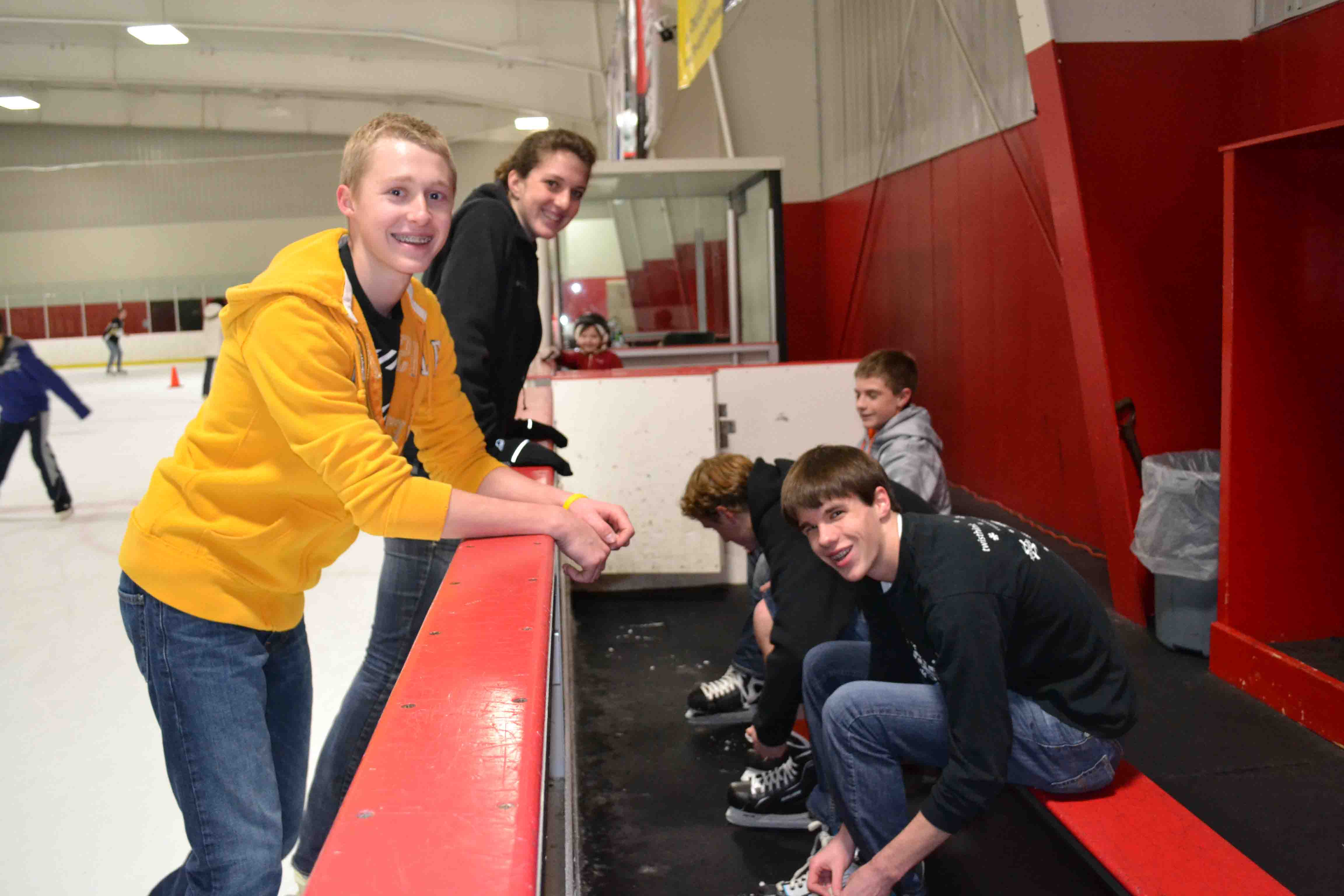 Trevor and Emily wait for Kray, Trey and Blake to lace up their skates.