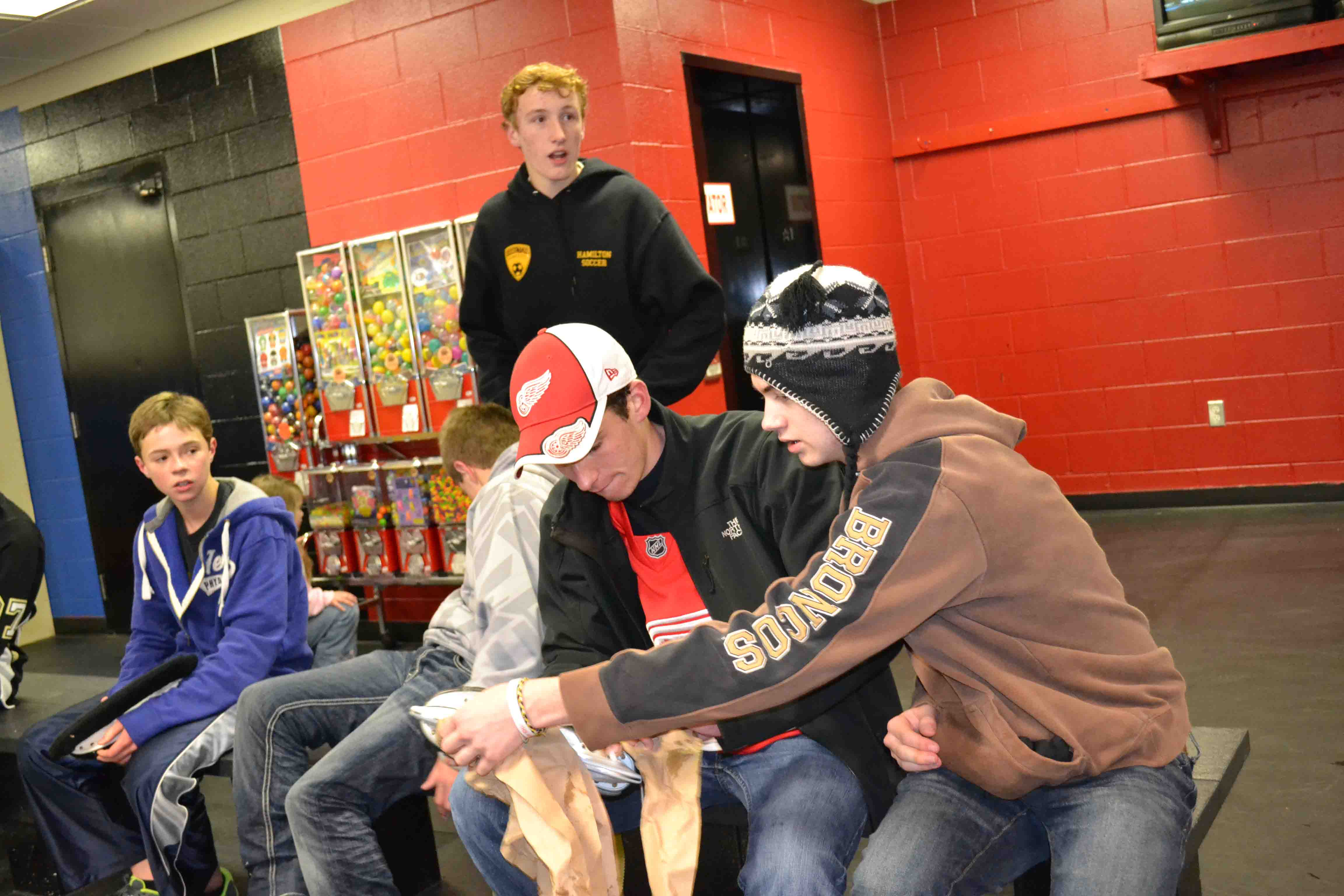 Brent shows Brett how to clean his skate blades, while Luke and Blake have a seat.